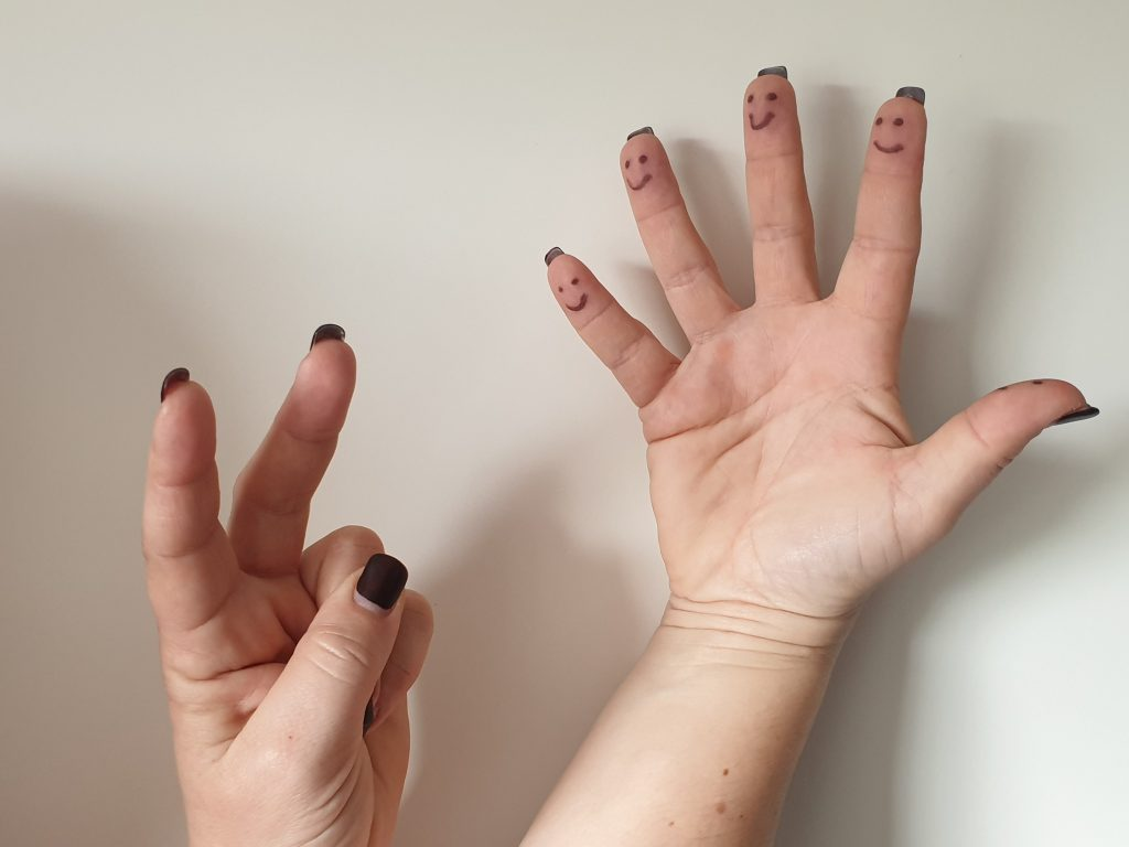 Male auf jeden Finger einer Hand ein Gesicht, die andere Hand, macht Hasenohren. © CMM