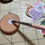 Die Holzscheiben (oder Steine) mit Serviettenlack einstreichen. © ausprobiert.at